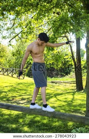 Attractive shirtless young man balancing on wooden bar in outdoor gym in city park - stock photo