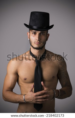 Attractive shirtless young man with black tie and top hat on dark background - stock photo