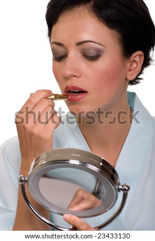 Attractive short hair brunette woman holding a make up mirror applying lipstick up close - stock photo