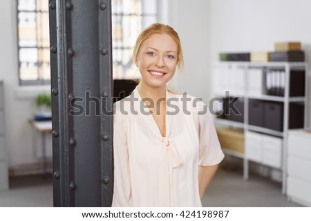 Attractive single young smiling female adult in light pink blouse leaning on post at work with bookshelf in background - stock photo