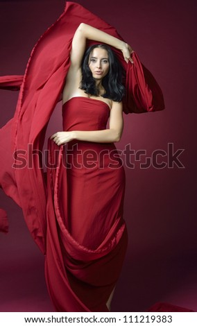 Attractive slender woman in long red fluttering dress on  red background - stock photo