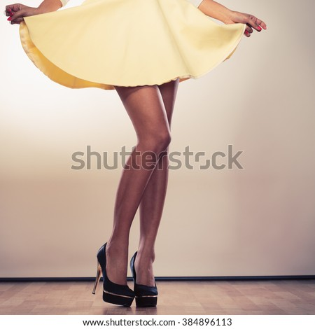 Attractive slim legs of mixed race african caucasian woman girl in skirt on high heels. - stock photo