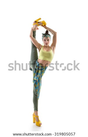 Attractive slim teen girl posing in studio. Full length portrait of young fashion woman. Fitness dancing girl. Splits. - stock photo