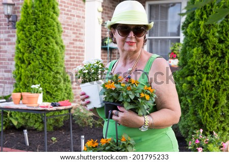 Attractive smiling active senior lady in sunglasses returning from the nursery with colorful ornamental flowering plants and seedlings to be transplanted into her garden during spring - stock photo