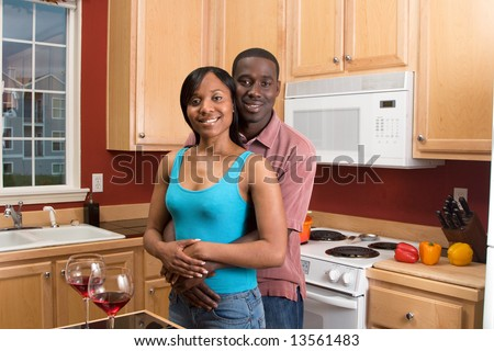 Attractive smiling African American couple standing in a kitchen. Horizontally framed shot with the man and woman looking at the camera. - stock photo