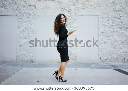 Attractive smiling business woman in black dress with long curly hair posing against a white brick wall with copy space area for your text o design and writing a text message on her digital smartphone - stock photo