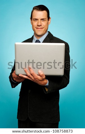 Attractive smiling businessman holding laptop and surfing web - stock photo