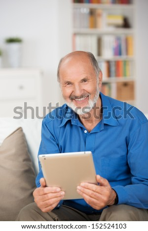 Attractive smiling elderly man holding a tablet-pc as he sits on a couch in his living room at home smiling at the camera - stock photo
