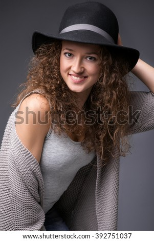 Attractive smiling girl in a studio on a black background. She looks at the camera with one hand down, while the other hand on his head. She wears dark blue jeans and a gray sweater. - stock photo