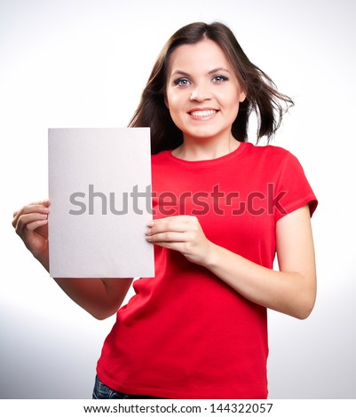 Attractive smiling girl in red shirt holding a poster,on white background. - stock photo