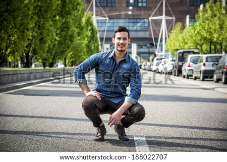 Attractive smiling man sitting in the middle of city road looking at camera - stock photo