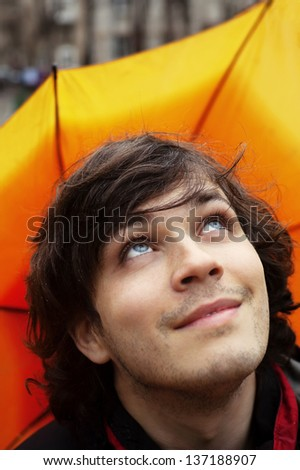 Attractive Smiling Man with Umbrella Checking Sky After Rain - stock photo