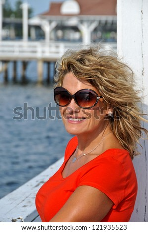 Attractive Smiling Middle Aged Woman Wearing Red Top Leaning against handrail with Ocean in the Background - stock photo