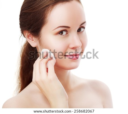 attractive smiling woman cleaning skin on white background - stock photo