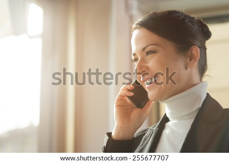 Attractive smiling woman having a phone call with her smart phone next to a window - stock photo