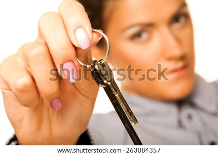 Attractive smiling woman holding up a key belonging to her house, isolated on white - stock photo