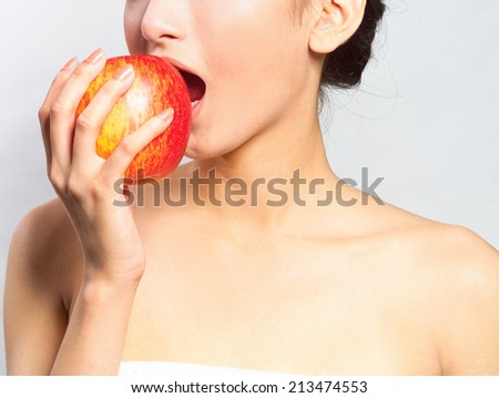 attractive smiling woman in towel eat red apple - stock photo