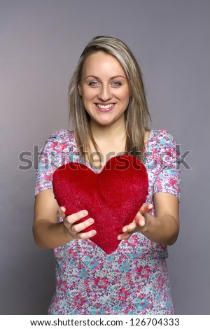 attractive smiling woman on gray background holding a red heart - stock photo