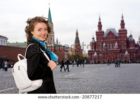 Attractive smiling woman standing on the Red Square in Moscow, Russia - stock photo