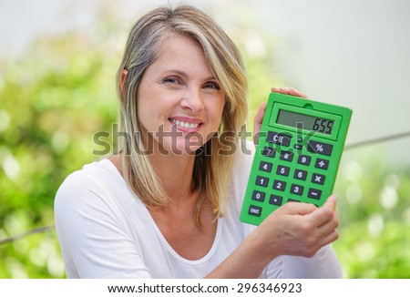 attractive smiling woman with calculator isolated on green background - stock photo