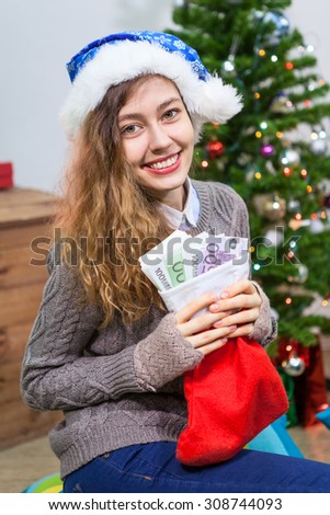 Attractive smiling woman with red Christmas sock and money inside - stock photo