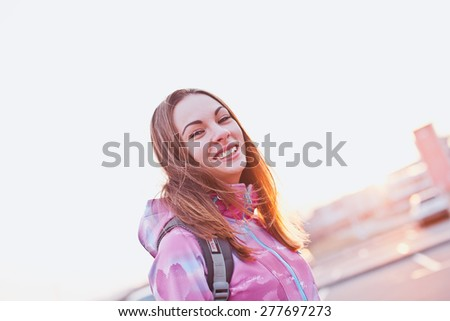 Attractive smiling young female looking to a camera on sunset. She travels through country with backpack and windbreaker. Freedom, happiness and tourism concept. Angle view - stock photo