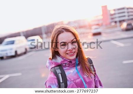 Attractive smiling young female with backpack straps on her shoulders. Stands on a parking lot in urban scenery at sunset. Looking right to camera - stock photo