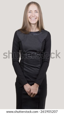Attractive smiling young woman in a black dress clasped her hands looking at camera. - stock photo