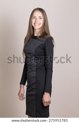 Attractive smiling young woman in a black dress looking at camera. - stock photo