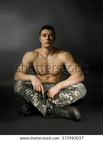 attractive soldier with athletic body with gun over dark background - stock photo