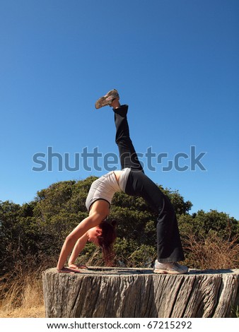 Attractive 20-something lady does a backbend on old tree stump on Angel Island in San Francisco Bay. - stock photo