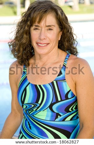 Attractive 50-something senior woman at an outdoor swimming pool. - stock photo