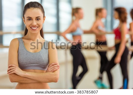 Attractive sport girl looking at camera and smiling while standing in fitness class, in the background girls talking - stock photo