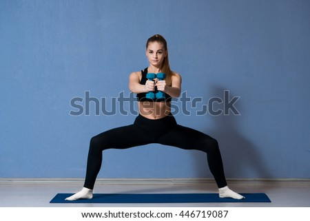 Attractive sport girl smiling and looking at camera while working out with dumbbells and doing lunges in fitness class - stock photo
