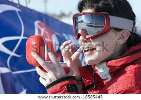 Attractive sport girl snowboarder applying face pack outdoors in winter mountain - stock photo