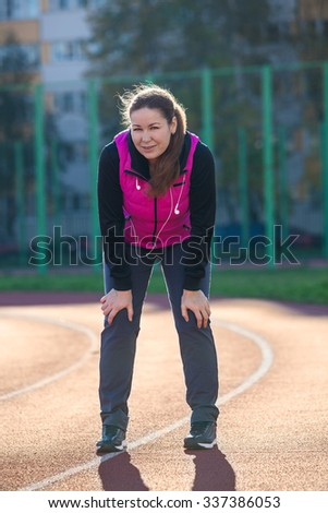 Attractive sportswoman resting at the stadium line while jogging - stock photo