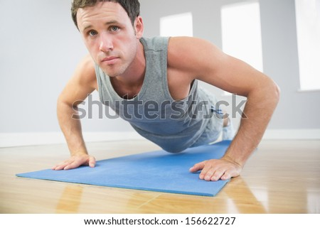 Attractive sporty man doing push ups on blue mat looking at camera in bright room - stock photo