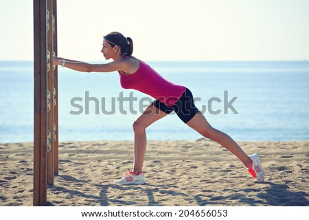 Attractive sporty woman with muscular body doing stretching exercise on the horizontal bar, workout outdoor, female runner on the beach, fitness and healthy lifestyle concept - stock photo