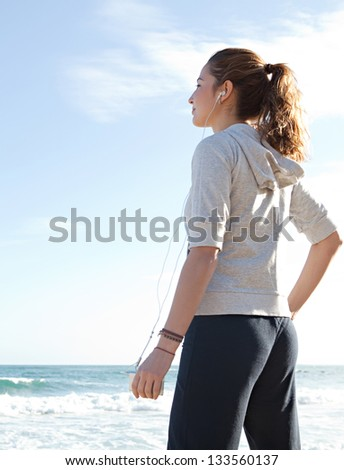 Attractive sporty young woman standing on the beach taking a break from exercising and listening to music with her mp4 player and head phones against a blue sky. - stock photo