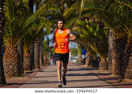 Attractive strong athlete jogging at evening - stock photo
