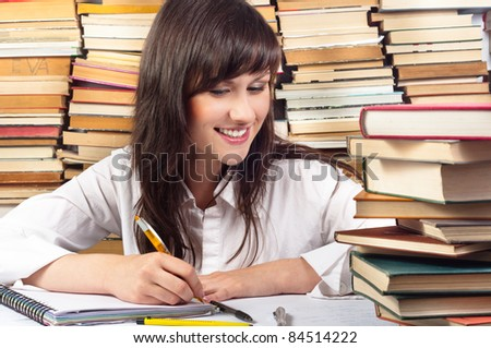 Attractive student girl writing her homework - stock photo