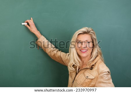 Attractive stylish blond woman teacher writing on a blank blackboard in class turning to watch her students - stock photo