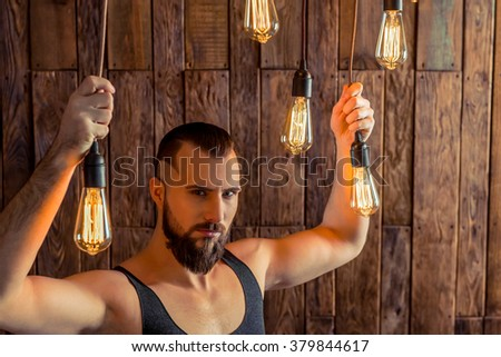 Attractive stylish man with beard in black singlet holding light bulbs, looking at camera, standing on a wooden background - stock photo