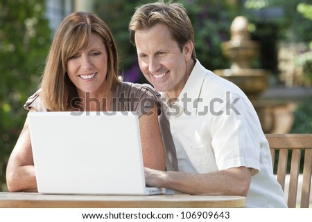 Attractive, successful and happy middle aged man and woman couple in their thirties, sitting together outside in a garden using a laptop computer. - stock photo