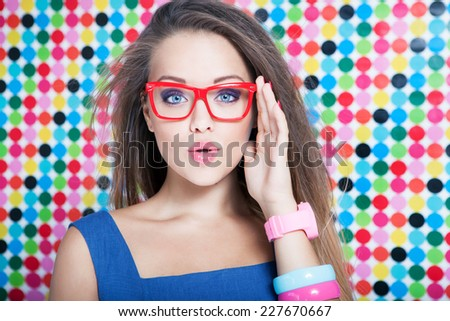 Attractive surprised young woman wearing glasses on spotted background, beauty and fashion concept  - stock photo