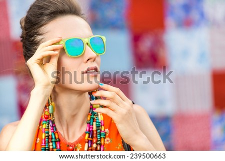 Attractive surprised young woman wearing sunglasses on checkered background, beauty and fashion concept. focus on lips and sunglasses - stock photo