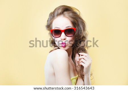 Attractive surprised young woman wearing sunglasses on gold back - stock photo