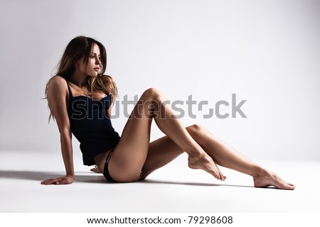 attractive tanned brunette in blue underwear sit on floor, full body shot, small amount of grain added, studio shot - stock photo