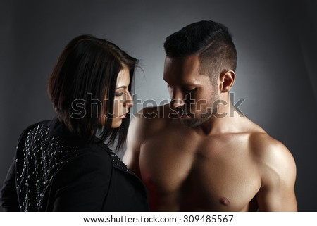 Attractive tanned dancers looking at each other - stock photo