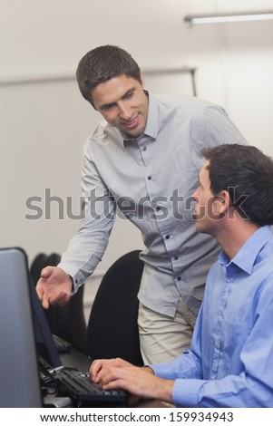 Attractive teacher talking to his student in computer class in college - stock photo